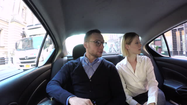 young couple in back seat at car, woman talking on phone, daytime - passenger seat stock videos & royalty-free footage