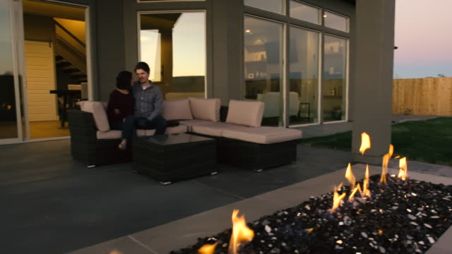 young couple in back yard at outdoor fireplace - patio stock videos & royalty-free footage