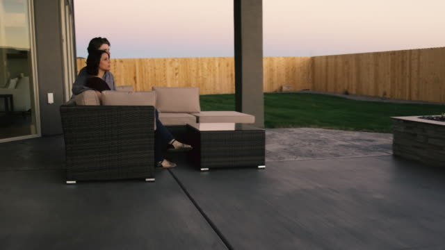 young couple in back yard at outdoor fireplace - teenage couple stock videos & royalty-free footage