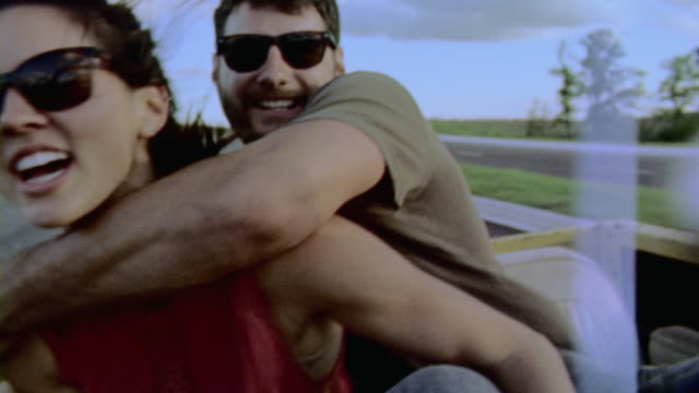 Young couple in backseat of classic Bronco hug and pose for film camera as driver laughs
