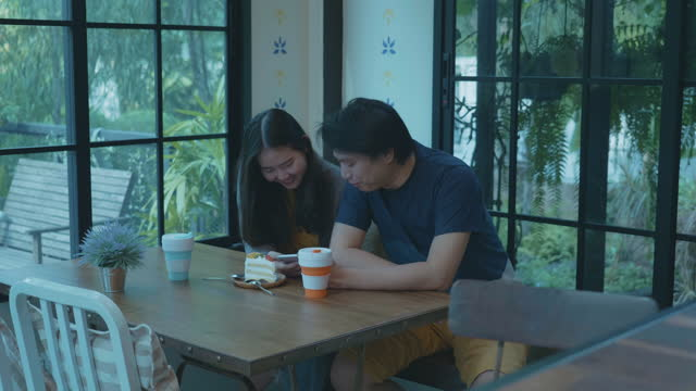 young couple in cafe with cake and reusable coffee cup - coffee cup stock videos & royalty-free footage