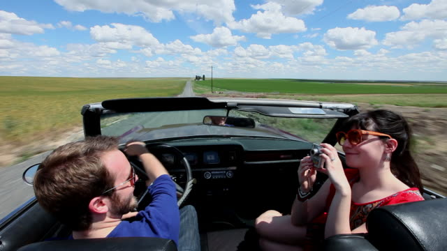 ws young couple in convertible taking self portrait with digital camera while driving on rural road through grain fields/washington, usa  - digital camera stock videos & royalty-free footage
