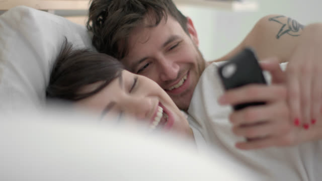 Young couple in hotel bed read texts on smartphone and laugh