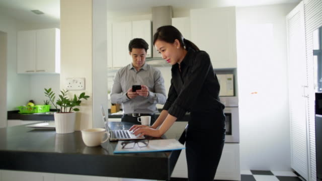MS Young couple in kitchen using laptop computer and smartphone