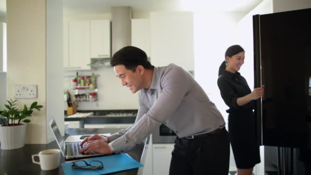 MS Young couple in kitchen with laptop