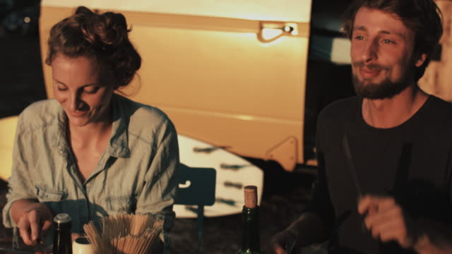 vídeos y material grabado en eventos de stock de young couple in love cooking dinner, eating dry spaghetti in front of vw bus and surfboard outside in campground in the south of france. - pareja joven