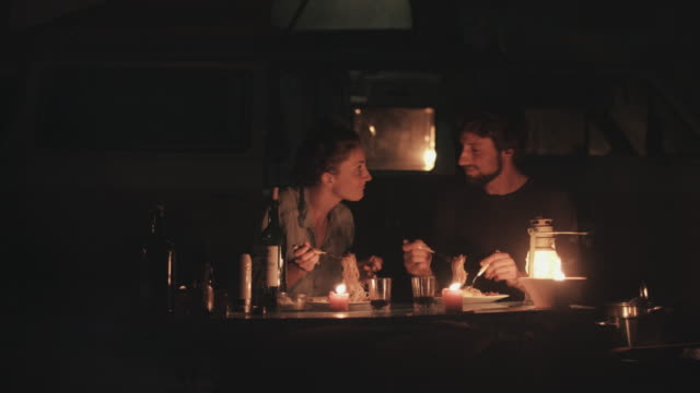 Young couple in love eating dinner at candle light in front of VW bus outside in campground in the south of France.