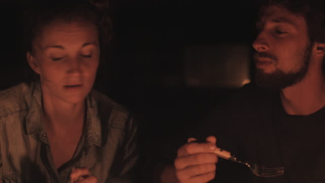 young couple in love eating dinner at candle light in front of vw bus outside in campground in the south of france. - candlelight stock videos & royalty-free footage