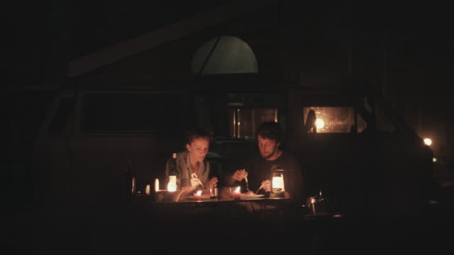 Young couple in love eating spaghetti at camping table outside in front of VW bus in candle light in campground in the south of France.