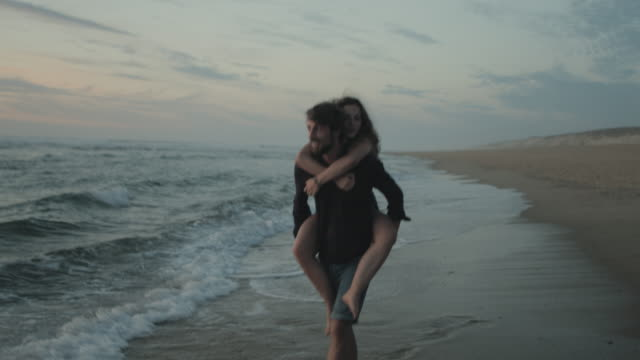 vídeos de stock e filmes b-roll de young couple in love enjoying time together, carrying piggyback, playing in water at sunset on a deserted beach at atlantic ocean in the south of france - namorado
