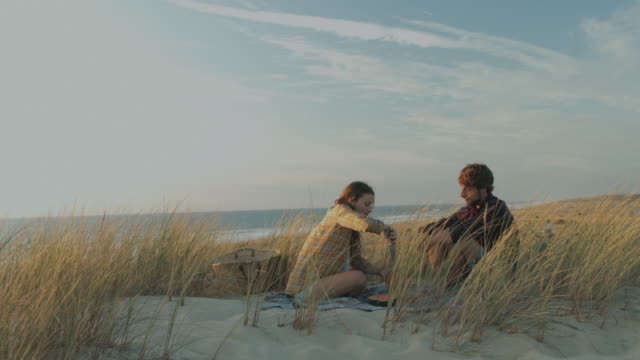 Young couple in love enjoying time together, eating watermelon, having picnic on dune on a deserted beach at Atlantic ocean in the south of France