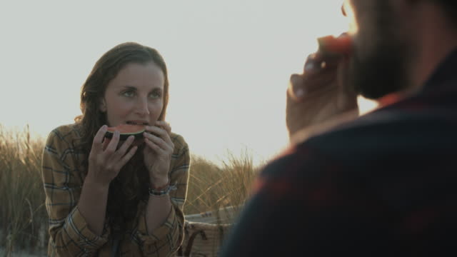 Young couple in love enjoying time together, eating watermelon, having picnic on dune on a beach at Atlantic ocean in the south of France