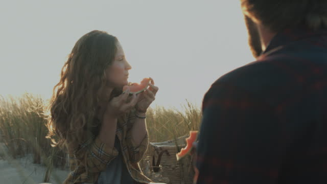 vídeos de stock e filmes b-roll de young couple in love enjoying time together, eating watermelon on dune on a beach at atlantic ocean in the south of france - picnic