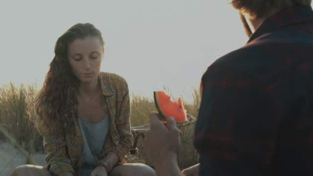 Young couple in love enjoying time together, eating watermelon on dune on a beach at Atlantic ocean in the south of France