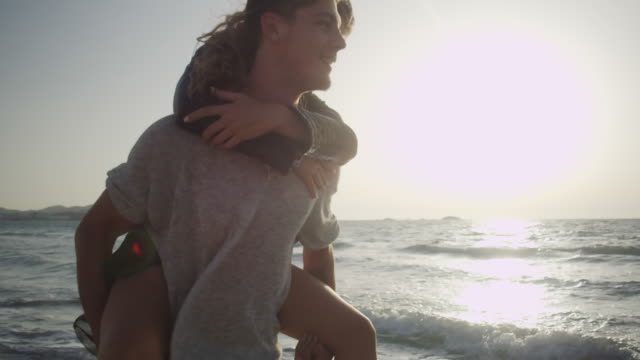 young couple in love enjoying time together on a beach - multiple shots available - piggyback stock videos & royalty-free footage