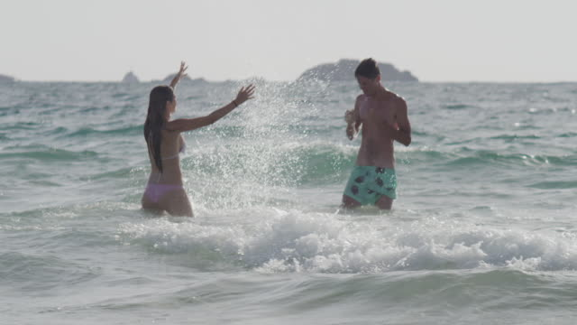 young couple in love enjoying time together on a beach - multiple shots available - young couple stock videos & royalty-free footage