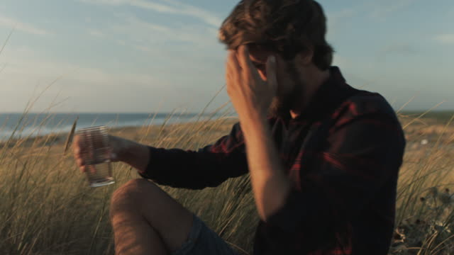 young couple in love enjoying time together, packing up picnic blanket on dune on a beach at atlantic ocean in the south of france - picnic stock videos and b-roll footage
