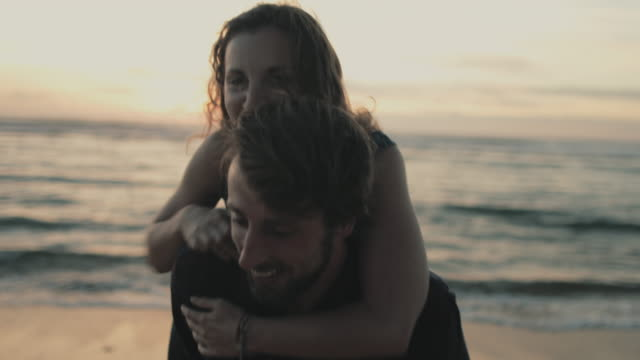 young couple in love enjoying time together, playing in water at sunset, carrying piggyback on a beach at atlantic ocean in the south of france - piggyback stock videos & royalty-free footage