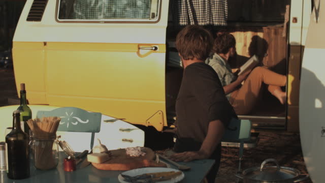 young couple in love enjoying time together, preparing dinner and reading book in front of vw bus at campground at atlantic ocean in the south of france - cutting board stock videos and b-roll footage