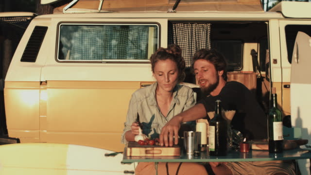 Young couple in love enjoying time together, preparing dinner outside in front of VW bus at sunset, flirting, tasting, cutting vegetables at campground in the south of France.