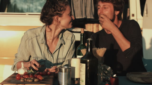 young couple in love enjoying time together, preparing food, cutting vegetables in front of vw bus in campground in the south of france - eating bildbanksvideor och videomaterial från bakom kulisserna