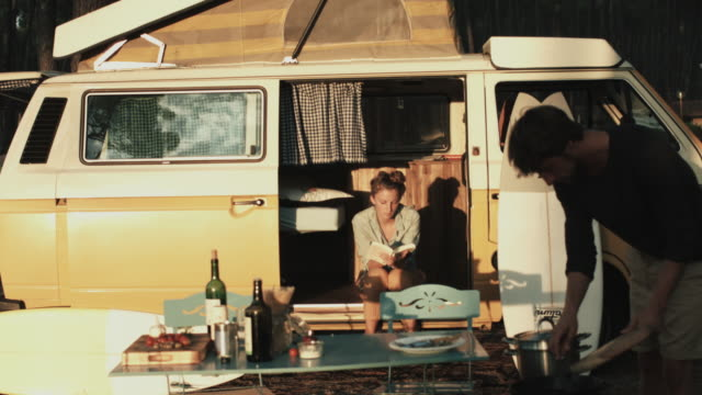 young couple in love enjoying time together, preparing food, reading, sitting in vw bus at campground in sunset in the south of france - holding stock videos & royalty-free footage