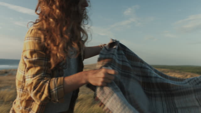 vidéos et rushes de young couple in love enjoying time together, putting down picnic blanket at sunset on dune on a beach at atlantic ocean in the south of france - panier de pique nique