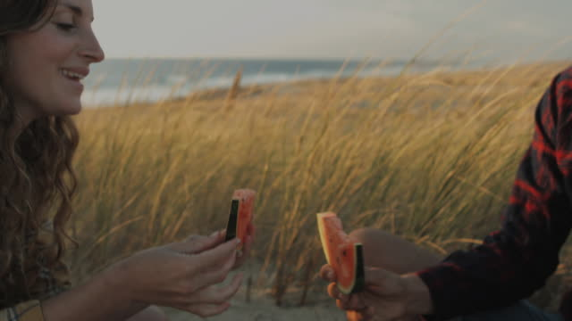 vídeos de stock e filmes b-roll de young couple in love enjoying time together, toasting with water melon on dune on a beach at atlantic ocean in the south of france - picnic