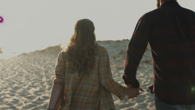 stockvideo's en b-roll-footage met young couple in love enjoying time together, walking to the beach with picnic basket at atlantic ocean in the south of france - hemden en shirts