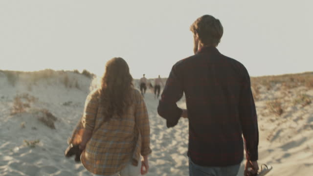 young couple in love enjoying time together, walking to the beach with picnic basket at atlantic ocean in the south of france - aquitaine stock-videos und b-roll-filmmaterial