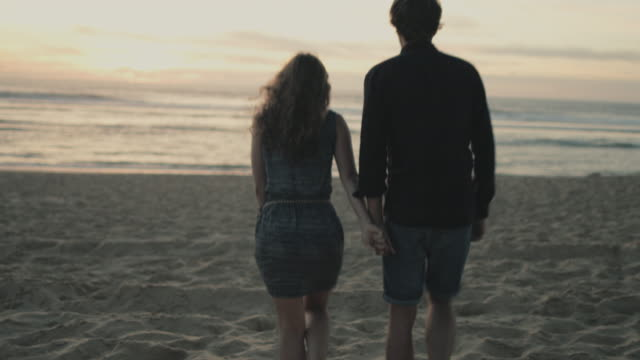 young couple in love enjoying time together, walking toward water at sunset on a beach at atlantic ocean in the south of france - hände halten stock-videos und b-roll-filmmaterial