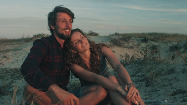 young couple in love enjoying time together, watching sunset from dune on a beach at atlantic ocean in the south of france - behaglich stock-videos und b-roll-filmmaterial