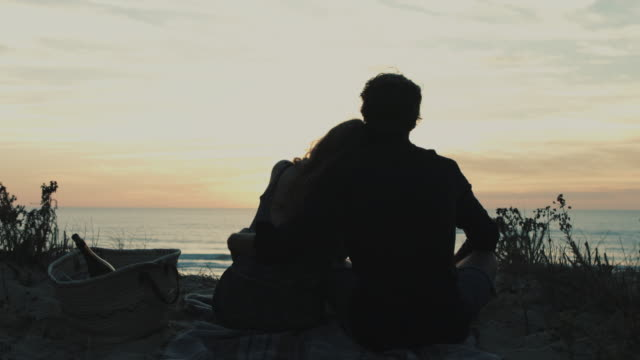 Young couple in love enjoying time together, watching sunset from dune on a beach at Atlantic ocean in the south of France