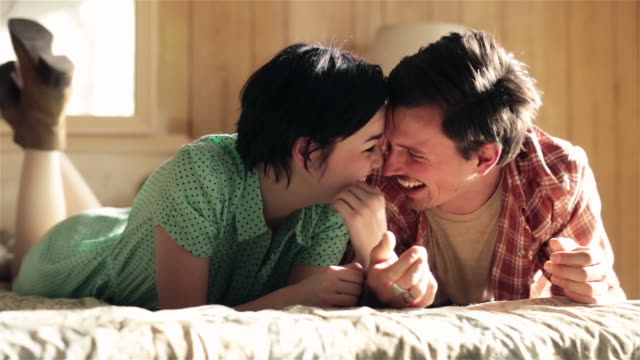 vidéos et rushes de young couple in love hold hands and nuzzle on motel bed - caresser