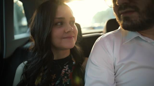 vidéos et rushes de jeunes couples dans la main de fixation d'amour tout en conduisant au siège arrière de la voiture - tomber amoureux