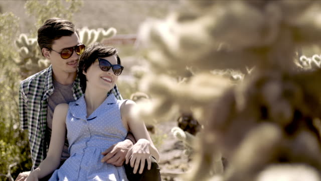 young couple in love kiss in cactus grove - hot kiss stock-videos und b-roll-filmmaterial