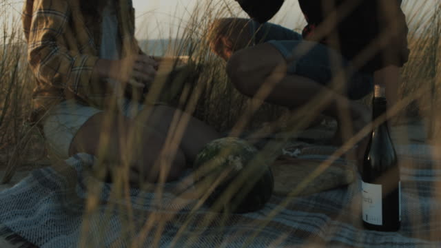 Young couple in love preparing picnic on dune at beach at Atlantic ocean in the south of France with water melon and wine on picnic blanket in sand