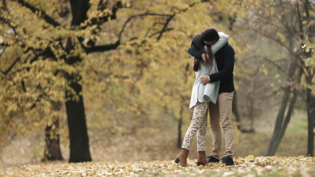 young couple in love showing affection toward each other during autumn day in nature. - young women stock videos & royalty-free footage