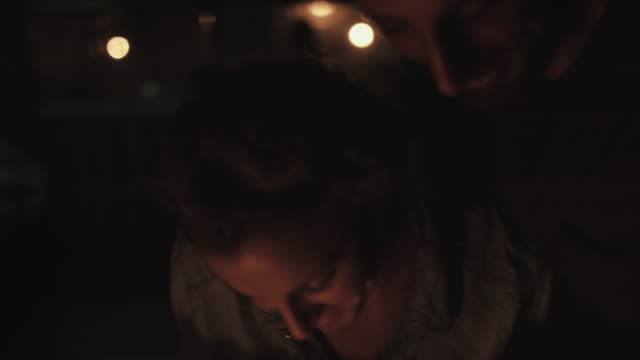 young couple in love spending time together, kissing in candle light in front of vw bus in campground in the south of france. - lagerfeuer stock-videos und b-roll-filmmaterial