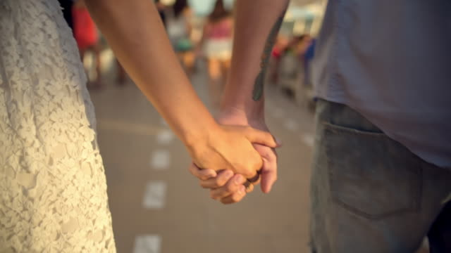 young couple in love walking while holding hands at mambobeach on the island of ibiza during sunset - 異性のカップル点の映像素材/bロール