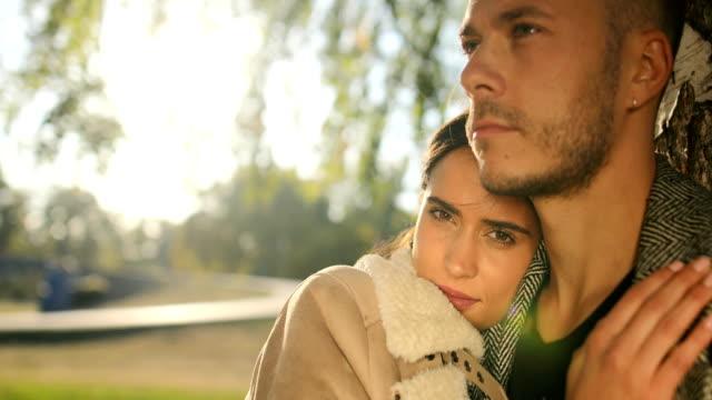 ungt par i parken vid trädet - gå tillsammans bildbanksvideor och videomaterial från bakom kulisserna