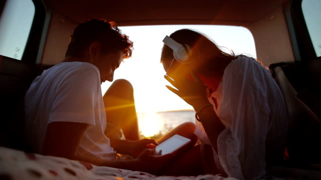 young couple in the car trunk on vacation.sea and sunset in background. - form of communication stock videos & royalty-free footage
