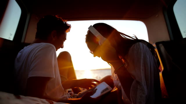 young couple in the car trunk on vacation.sea and sunset in background. - ascoltare video stock e b–roll