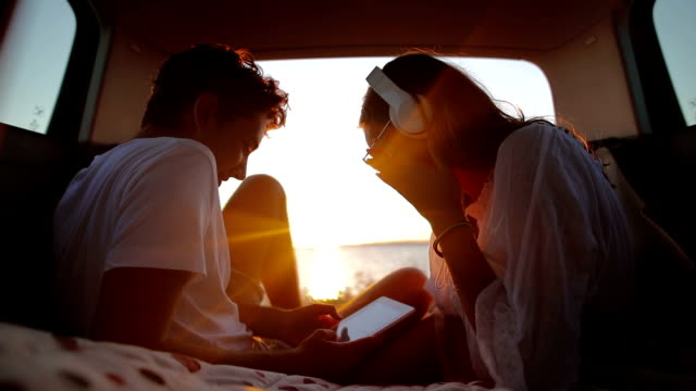 young couple in the car trunk on vacation.sea and sunset in background. - camping stock videos & royalty-free footage