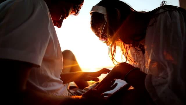 vídeos y material grabado en eventos de stock de pareja joven en el maletero del coche de vacaciones. mar y puesta de sol en el fondo. - libertad