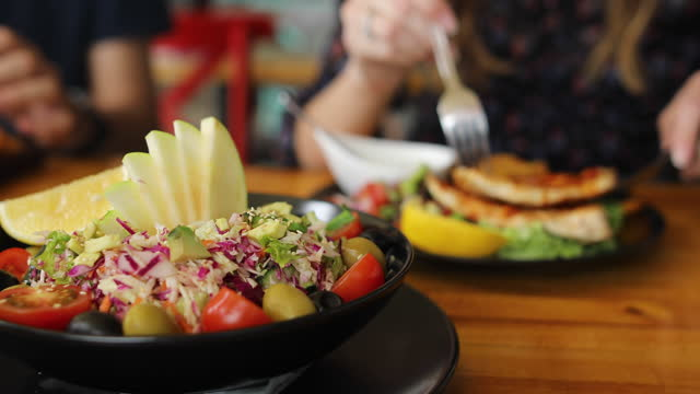 young couple in the restaurant. colorful poke bowl with roasted sesame prawns, red cabbage, avocado, cherry tomatoes, corn salad and lettuce,apple and olives - red cabbage stock videos & royalty-free footage