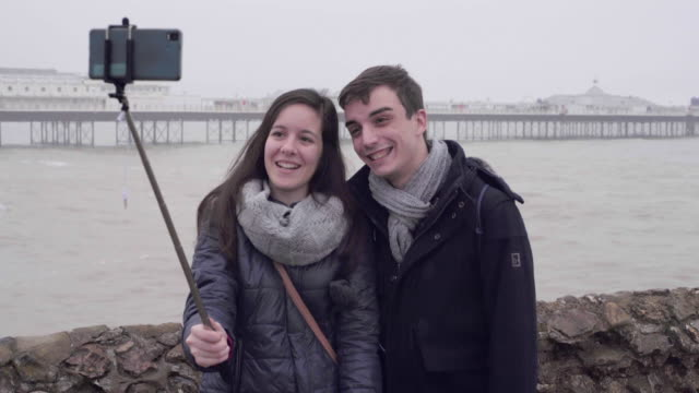 A young couple in winter taking a selfie on the beach.