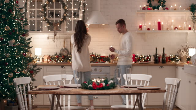 A young couple is preparing for the arrival of guests for Christmas dinner. They set the Christmas table in the living room, light candles.