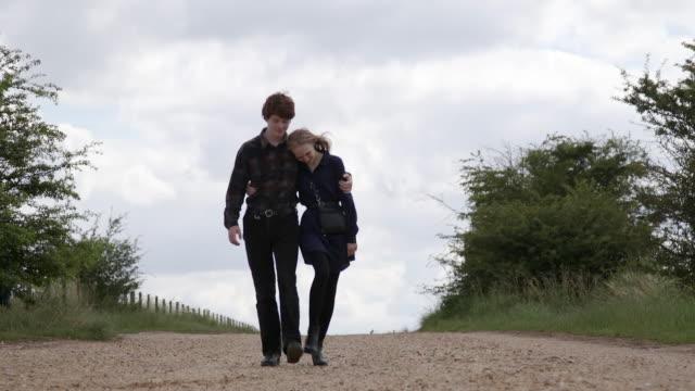 vídeos de stock, filmes e b-roll de young couple is walking down the hill - overcast