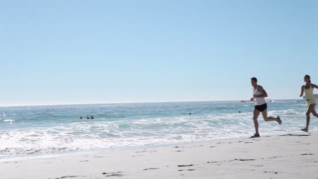 stockvideo's en b-roll-footage met young couple jogging on beach - gymbroek